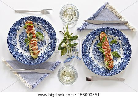 Plates with baked courgette with tomatoes and cheese glasses with white wine romantic dinner for two. Homey atmosphere clean white table. Top view