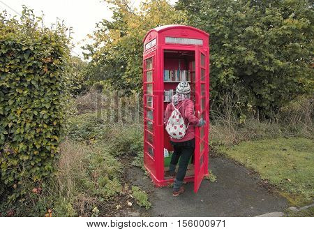 Hargrave Cheshire UK - October 22 2016: Red phone booth converted to a book share. Young Woman borrows book.