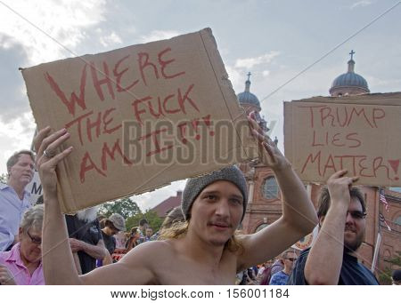 Asheville North Carolina USA - September 12 2016: Young male protesters at a Trump campaign rally hold signs saying