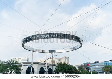Houston, USA - August 14, 2016: Houston, Uptown District Post Oak Boulevard unique circular stanless steel reflecting street direction sign held by wires across the intersection with car reflections in shiny surface