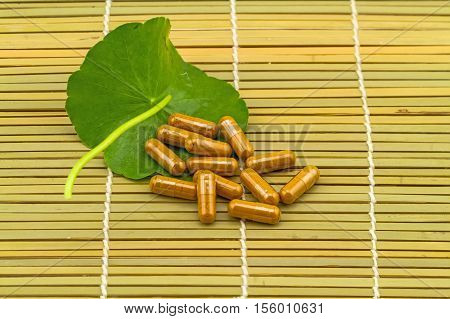Green Asiatic Pennywort (Centella asiatica ) and yellow pill capsules on brown bamboo weave background