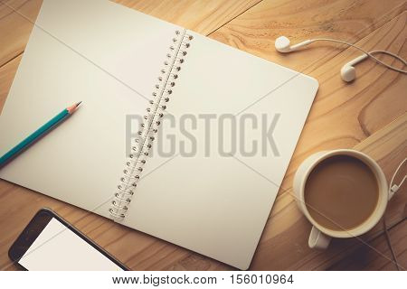 Relax workplace - Top view of Smartphone with blank screen earphones notebook and coffee on wooden background vintage tone