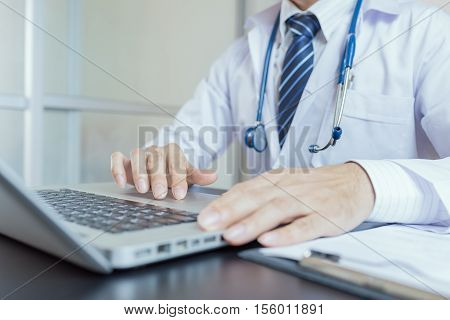 Close-up of a medical worker typing on laptop. Doctor man. Doctor woman. Uniform doctor. Doctor concept. Doctor using laptop. Doctor using notebook. Doctor using computer.