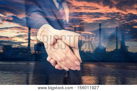 Double exposure of handshake and refinery. handshake on refinery background. refinery on sunrise. Business concept.  Business shake hand. Refinery concept.