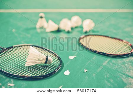 Badminton ball (shuttlecock) and racket on court floor. Vintage tone. Badminton sports. Play badminton. Badminton exer cise. Badminton tournament. Badminton training. Badminton feather. Badminton health. Shuttle badminton.