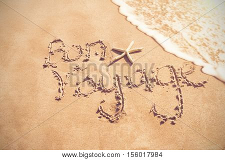 Bon voyage written on sand at beach
