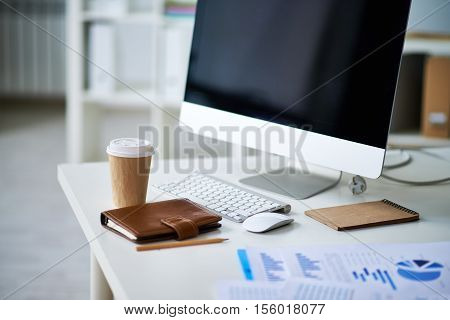 Workplace in modern office: computer, disposable coffee cup, documents, notepad and personal organizer on the desk