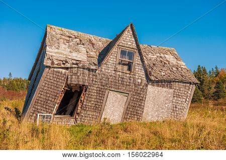 crooked leaning old house over blue sky