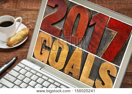 2017 goals banner - New Year resolution concept -  text in vintage letterpress wood type printing blocks stained by red ink on a laptop screen with a cup of coffee