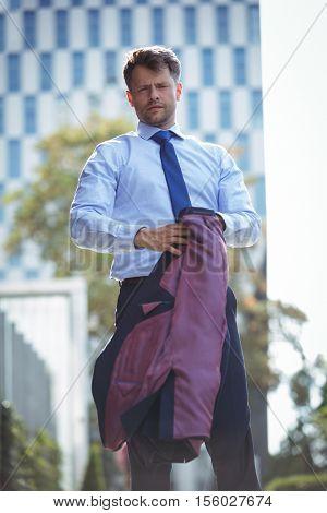 Portrait of handsome businessman holding blazer near office building