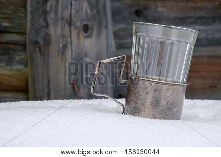 Empty old cup in the cup holder on the snow-covered table
