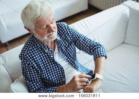 Senior man adjusting a time on smartwatch in living room at home