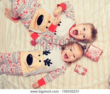 Little boy and girl lie on the bed with gift in pajamas.