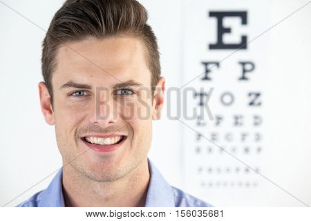 Portrait of man wearing contact lens with eye chart in background