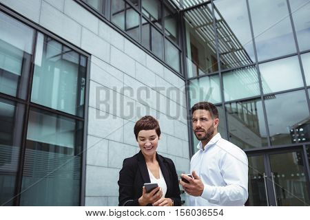 Businesspeople using mobile phone in office premises