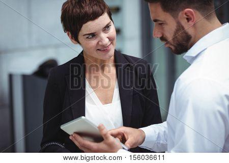 Businesspeople using digital tablet in office premises