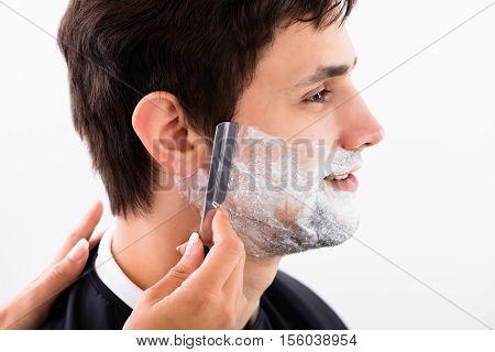 Close-up Of A Hairdresser Shaving Man's Beard By Applying Shaving Cream