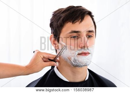 Hairdresser Shaving Young Man's Beard With Razor At Salon