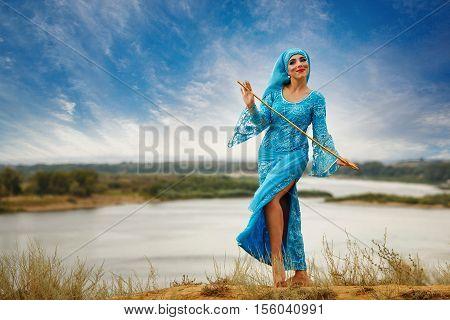 Oriental beauty Sa'idi dance. Nice girl in national dress dancing shepherdess with shepherd's cane outdoors. Nomads.