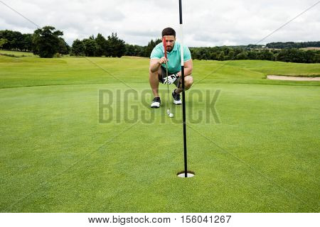 Man squatting to line up his putt in golf course