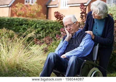 Depressed Depressed Senior Man In Wheelchair Being Pushed By Wife
