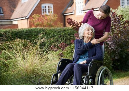 Adult Daughter Pushing Senior Mother In Wheelchair