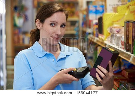 Sales Assistant Checking Stock Levels In Supermarket Using Hand Held Device