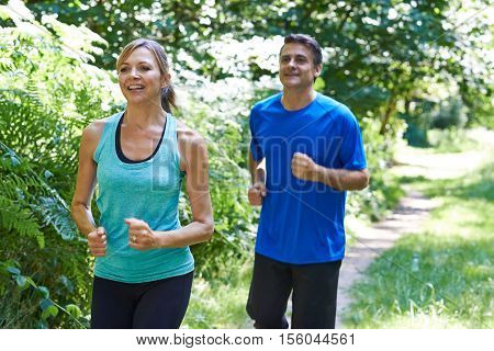 Mature Couple Running On Path In Countryside