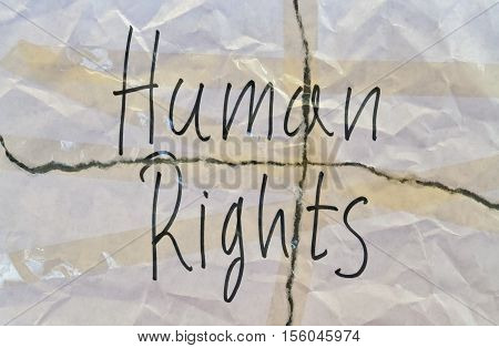 Text Human Rights written on torn white paper