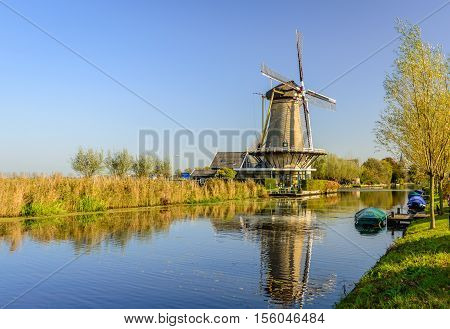Dutch polder landscape near the village of Bleskensgraaf with a windmill and a canal with some colorful covered boats on a sunny day in the fall season.