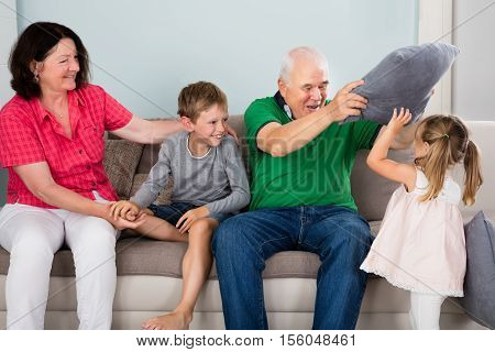 Older Happy Grandparents Having Pillow Fight With Kids On Couch Together At Home