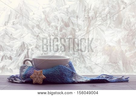 White empty mug for warming beverage wrapped in a scarf on a table next to a frosty winter window / time pour hotter