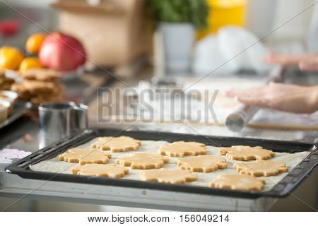 Christmas gingerbread cookies in a row on a tray, on the baking paper, ready to be baked in the oven. Hands with metal rolling pin on the background. Closeup, home, Christmas concept photo