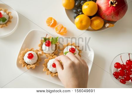 Gorgeous colorful berry tartlets with custard cream served for a dinner party, fruits, hand picking a red cherry. Closeup, lay flat