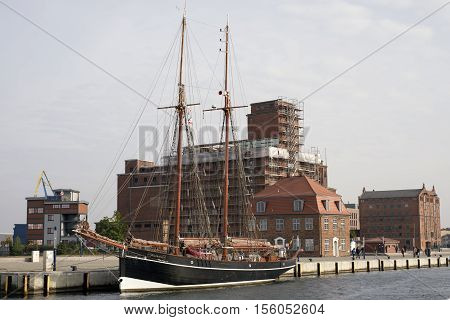 WISMAR GERMANY - OCTOBER 14 2016: Part of the old harbor in Wismar with old ship Atalanta and old building Baumhaus October 14 2016 Germany.