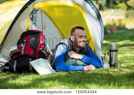Smiling hiker lying in tent at forest