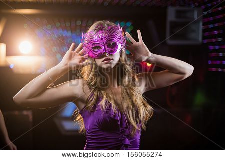 Portrait of woman with masquerade dancing on dance floor in bar