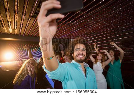 Man taking a selfie from mobile phone while friends dancing on dance floor at bar