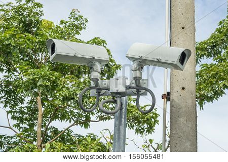 security CCTV cameras on a pole with the green tree background