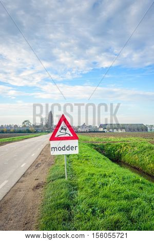 Traffic sign indicating mud in an agrarian landscape in Dutch. It's autumn and harvest time for sugar beets and a lot of mud is on the rural roads.
