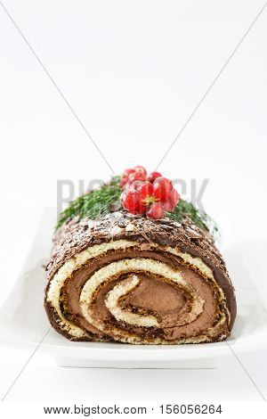 Chocolate yule log cake with red currant isolated on white background