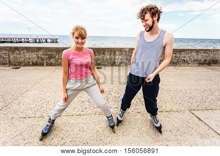 Two People Exercise At Seaside Ride Rollerblades.