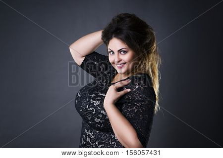 Young beautiful plus size model in black lace dres xxl woman portrait on gray studio background makeup and hairstyle