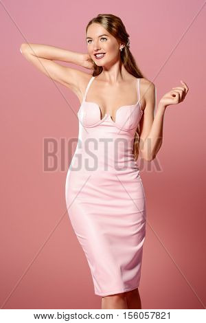Amazing woman wearing elegant fitting dress alluring over pink background. Beauty, fashion concept. Evening dresses collection.