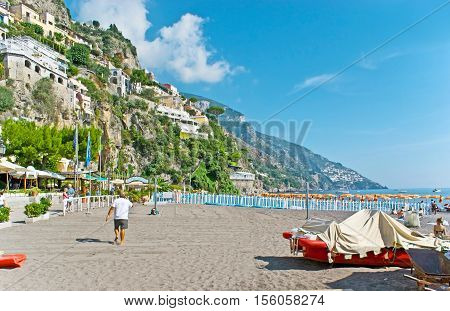 POSITANO ITALY - OCTOBER 5 2012: The walk along Marina Grande lying at the foot of the steep rock with villas and hotels cafes and restaurants of the picturesque resort on October 5 in Positano.