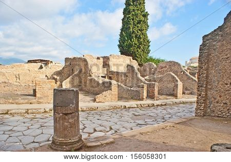 The ruined stone walls and columns on both side of the ancient street covered with paving stone Pompeii Italy.