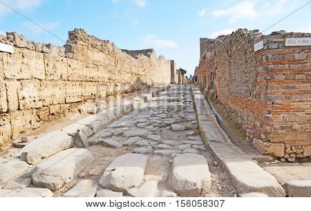The ancient road in Pompeii covered with paving stone and the large boulders served for pedestrians to cross the street Italy.
