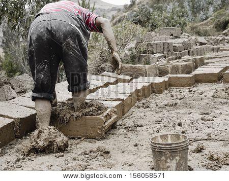 Boy Making Traditional Adobe Mud Bricks In Paru Paru Community Village, Pisaq District, Cusco Region