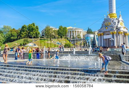 KIEV UKRAINE - SEPTEMBER 8 2016: The kids play in fountain in Maidan Nezalezhnosti (Independence Square) with the flower clock and October Palace on background on September 8 in Kiev.