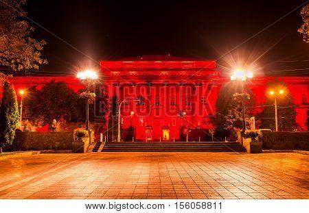 The red building of National University of Taras Shevchenko in bright red illumination Kiev Ukraine.